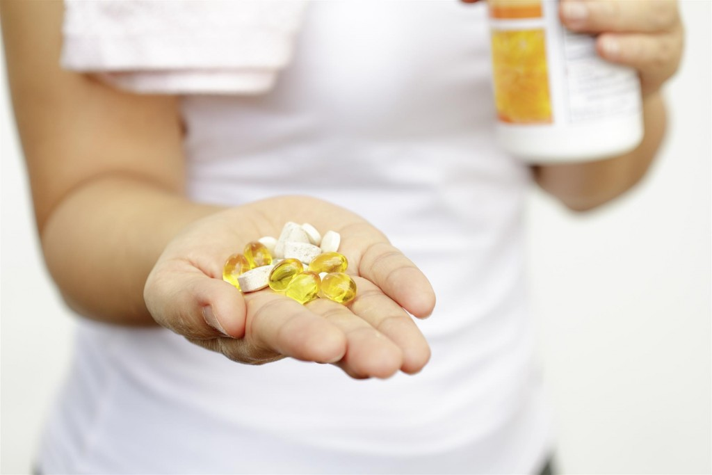 woman holding vitamins and medication