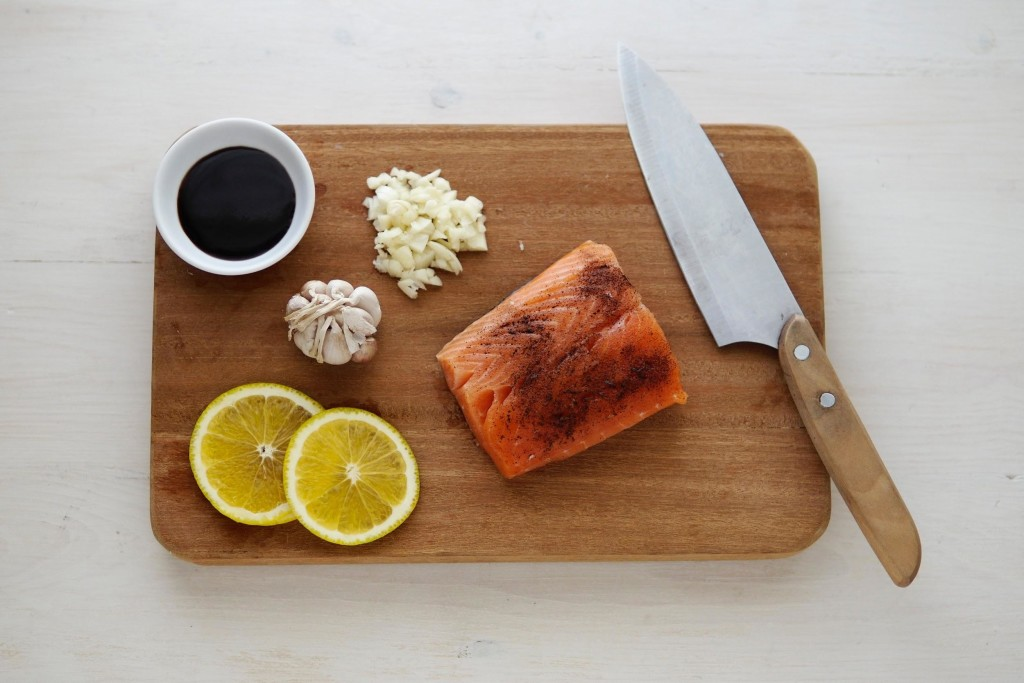 gray knife and orange salmon on wooden chopping board