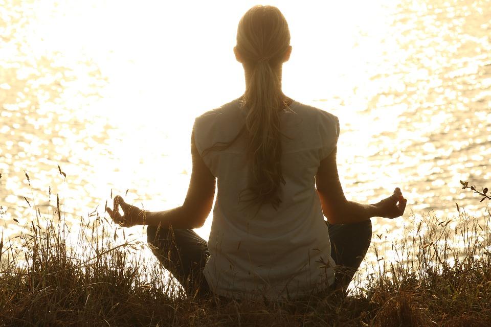 woman yoga exercises in park near lake