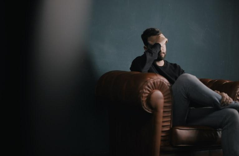 sad man sitting on the sofa and holding his forehead