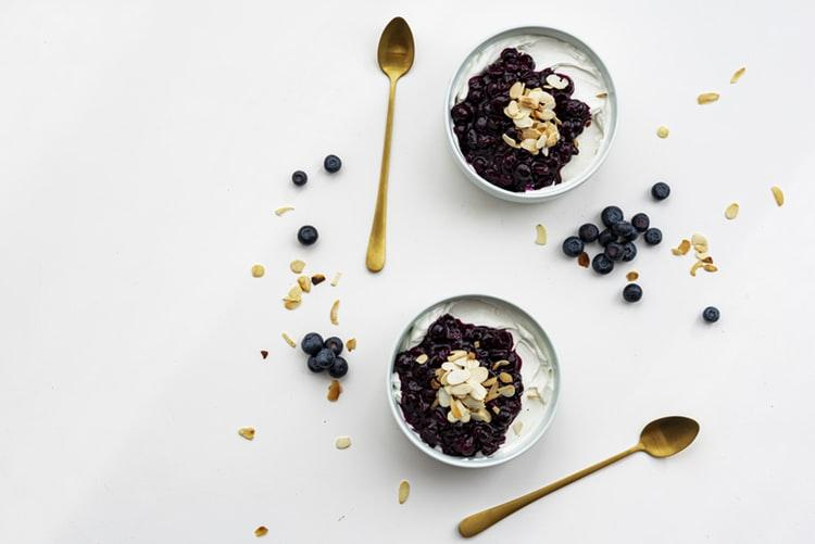 chia pudding dessert with blueberries and oatmeal on white wooden surface