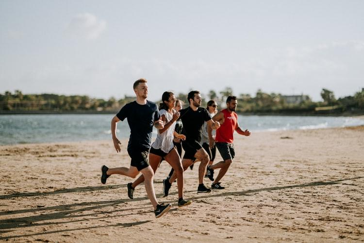 group of young friends together running on the beach