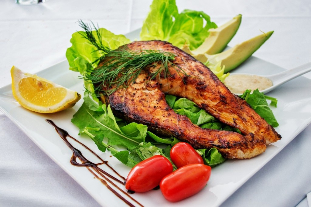 Grilled fish decorated with leaves of lettuce and cherry tomato