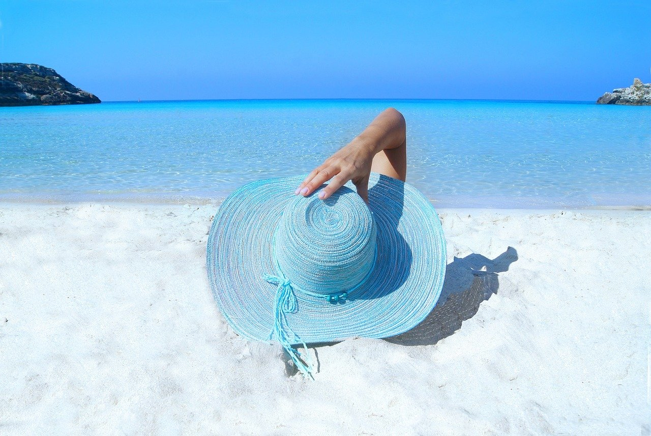 Woman wearing a blue hat and relaxing in the beach.