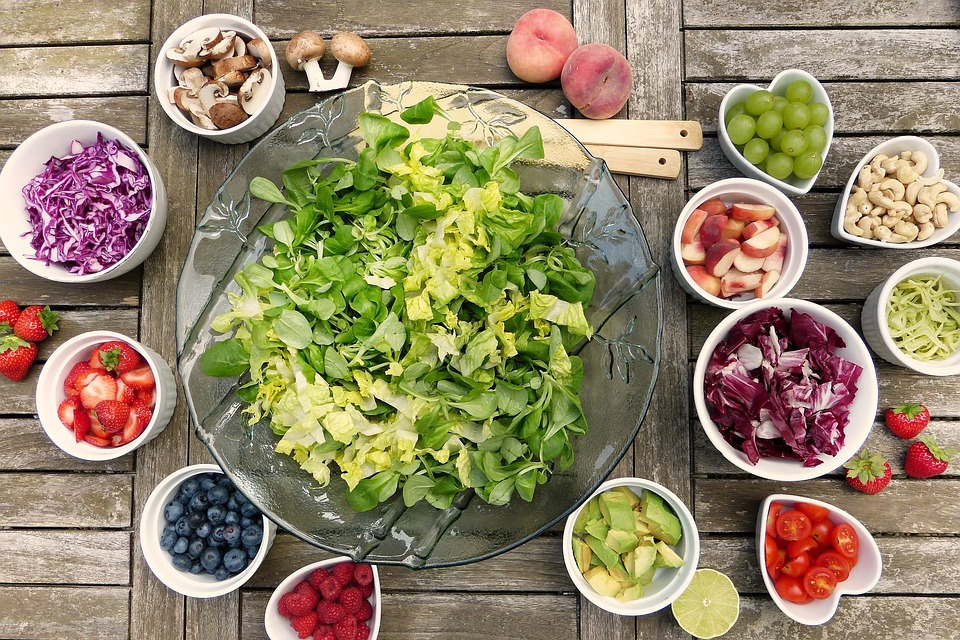 Fresh Salad isolated on wooden background with small bowls