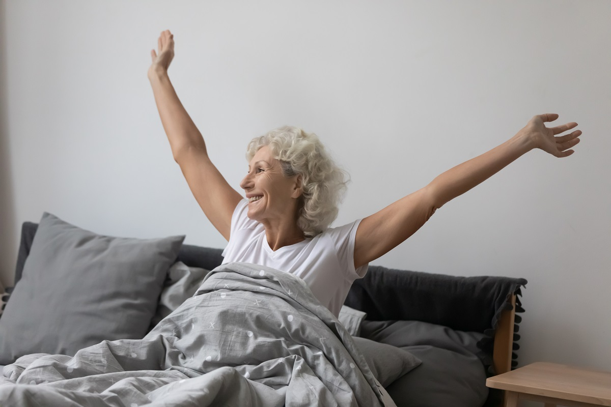 Happy mature woman wake up in bed stretching