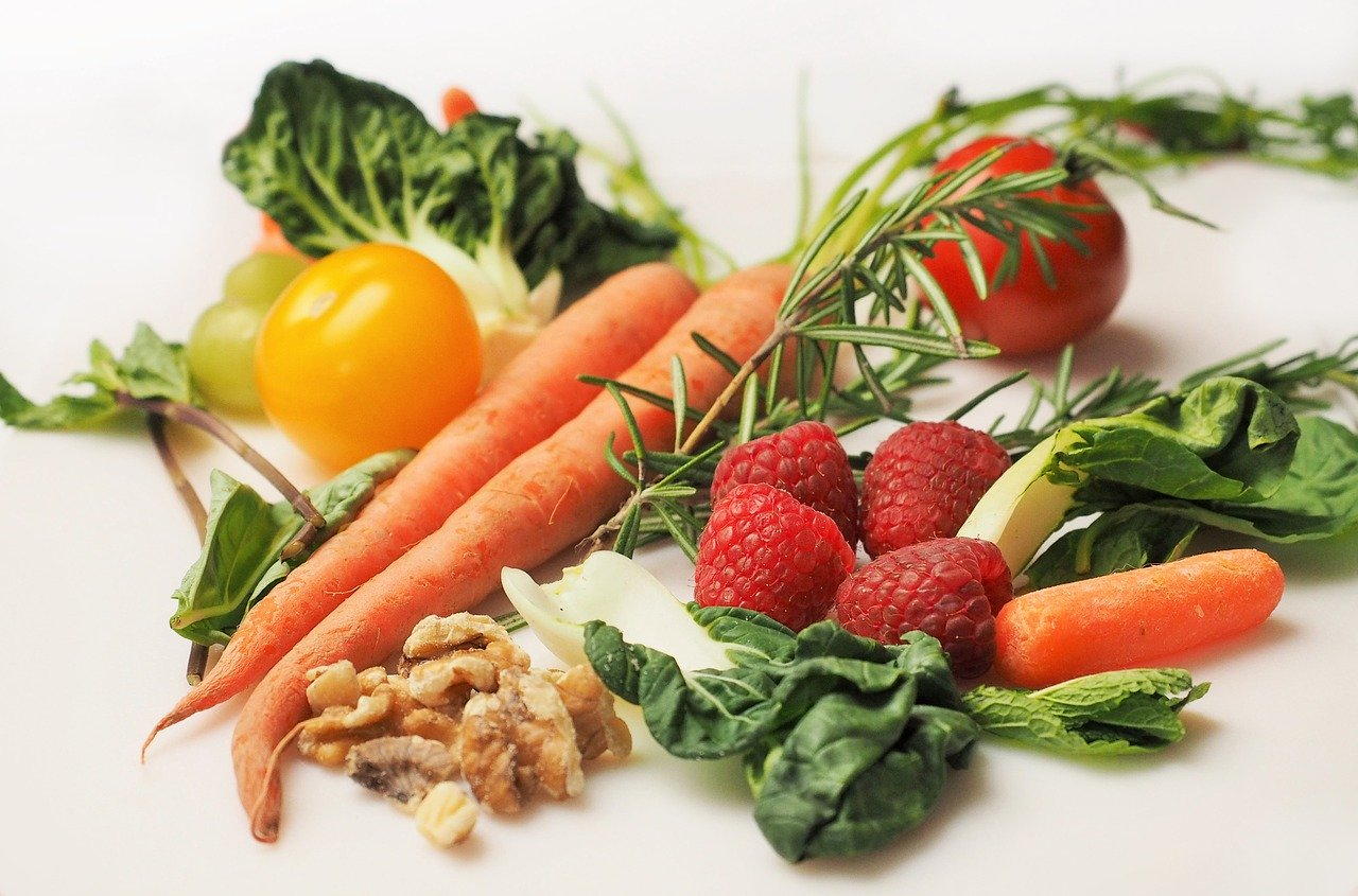 A collection of fruits and vegetable carrots, raspberries, tomatoes and pak choi