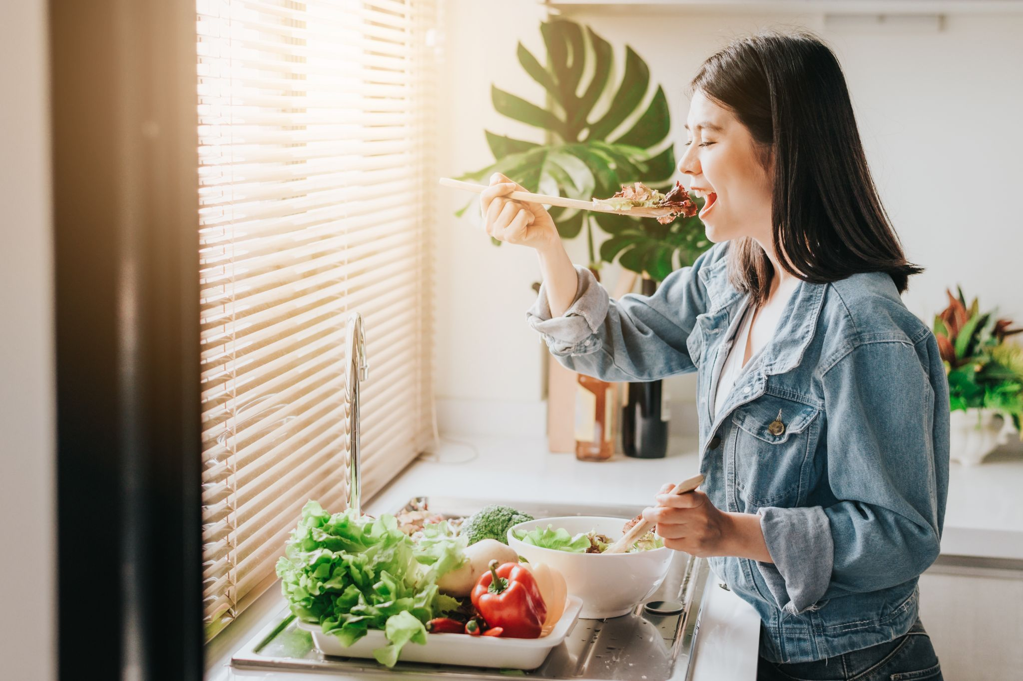 Happy woman eating fresh vegetables while preparing salad in kitchen